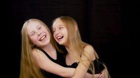 Het portret van huged mooie jonge meisjesvrienden die geïsoleerde besnoeiing bevinden zich bij het zwarte donkere glimlachen en l stock videobeelden