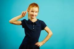 Het portret van intelligent rood haired meisje met opgeheven naar omhoog wijsvinger, heeft een gelukkig expressief gezicht, drukt stock afbeelding