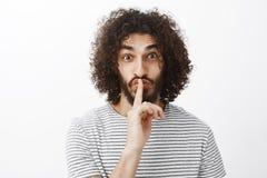 Het portret van intigued aantrekkelijke krullend-haired kerel met baard, status die opgewekt over grijze achtergrond, shh terwijl stock afbeeldingen