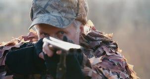 Het portret van jager in de doelstellingen van het de jachtmateriaal met het geweer, ligt in wachttijd op het gebied in zonsonder stock videobeelden