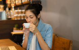 Het portret van jong Aziatisch schitterend wijfje met haar ogen sloot het genieten van de van geur van verse heerlijke koffie bij stock afbeelding