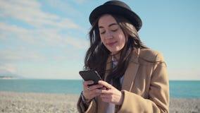Het portret van jong brunette verzendt berichten door smartphone op kustgebied stock videobeelden
