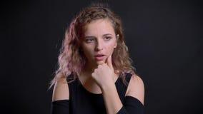 Het portret van jong Kaukasisch meisje met roze haar die zich zorgvuldig krijgt een inzicht op zwarte achtergrond bevinden stock videobeelden