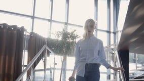 Het portret van jong model gaat beneden in zonnige zaal met glasmuur, langzame motie stock footage