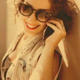 Het portret van jong mooi krullend donkerbruin meisje in zonnebril met rode lippen die telefoon spreken doet selfi Royalty-vrije Stock Foto's