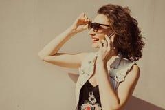 Het portret van jong mooi krullend donkerbruin meisje in zonnebril met rode lippen die telefoon spreken doet selfi Royalty-vrije Stock Foto