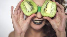Het portret van jong mooi krullend meisje met creatief maakt omhoog het behandelen van ogen met twee fruitige delen van kiwi stock videobeelden