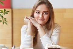 Het portret van jong mooi model zit in cafetaria, draagt slimme witte kleding, zet haar hoofd op handen Blauw eyed aanbiddelijk m stock afbeeldingen