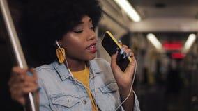 Het portret van jonge Afrikaanse Amerikaanse vrouw die met hoofdtelefoons aan muziek luisteren, zingt en het grappige dansen in o stock video