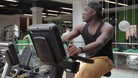 Het portret van jonge Afro-Amerikaanse sportman die aan zijn quadriceps werkt en op exercycle in de gymnastiek verlamt stock videobeelden