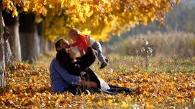 Het portret van jonge familie in de herfstpark, ouders speelt met baby, zonnige dag stock videobeelden