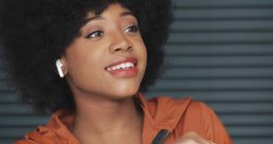 Het portret van jonge gelukkige Afrikaanse Amerikaanse vrouw die oortelefoons dragen, luistert aan muziek en het grappige dansen  stock videobeelden