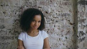 Het portret van het jonge glimlachen mengde rasvrouw het flirten en het onderzoeken van camera op bakstenen muurachtergrond Stock Afbeeldingen