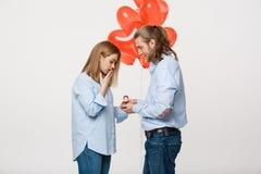 Het portret van Jonge knappe kerel geeft een ring aan een meisje op een witte achtergrond met de rode ballons van de hartlucht Stock Foto's