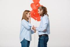 Het portret van Jonge knappe kerel geeft een ring aan een meisje op een witte achtergrond met de rode ballons van de hartlucht Stock Afbeeldingen