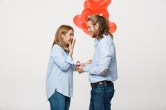 Het portret van Jonge knappe kerel geeft een ring aan een meisje op een witte achtergrond met de rode ballons van de hartlucht Stock Foto