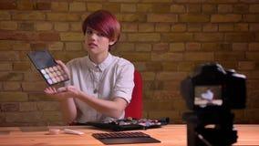 Het portret van jonge kortharige vrouwelijke schoonheid die actief over haar hulpmiddelen in camera spreken bricken muur stock video