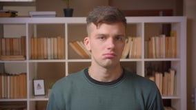 Het portret van jonge mannelijke student die nadenkend luistert en neigt aan toont meningsverschil en weigering bij bibliotheek z stock footage