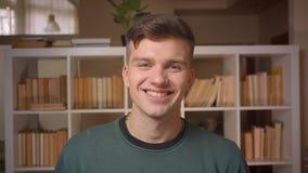 Het portret van jonge mannelijke student draait aan camera en horloges gelukkig in het die zich in bibliotheek bevinden stock footage