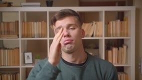 Het portret van jonge mannelijke student voert vreemde en grappige dansen aan de muziek uit die koel en ontspant bij bibliotheek  stock video