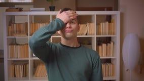 Het portret van jonge mannelijke studentengebaren facepalm ondertekent het behandelen van gezicht met hand bij bibliotheek stock videobeelden
