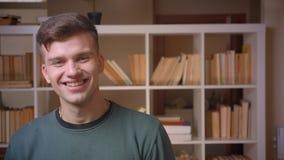 Het portret van jonge mannelijke studentengolven overhandigt en glimlachen in camera die uiterst blij in bibliotheek zijn stock video