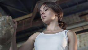 Het portret van het jonge meisje kiest tussen een militair GLB en een kroon van tarwe in de verlaten bouw Ongelukkige vrouw stock video