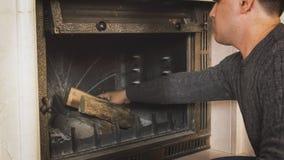 Het portret van jonge mens houten werpen opent open haard bij woonkamer het programma royalty-vrije stock fotografie