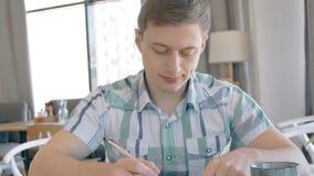 Het portret van jonge mens het schrijven langs ballpen in van hem indient koffie, langzame motie stock videobeelden