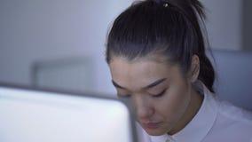 Het portret van jonge mooie vrouw in bedrijfskleren werkt bij lijst met zilverachtige PC 4k, zitting, die bekijken stock videobeelden
