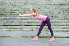 Het portret van jonge sportieve vrouw in sportkleding doet uitrekkende oefeningen openlucht royalty-vrije stock foto
