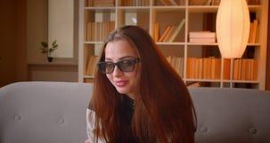 Het portret van jonge tiener in 3d glazen let op film thuis op TV-zitting op bank op boekenrekkenachtergrond stock footage