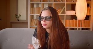 Het portret van jonge tiener in 3d glazenhorloges filmt thuis op TV-zitting op bank op boekenrekkenachtergrond stock footage