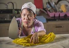 Het portret van jonge vrij gefrustreerde en beklemtoonde Aziatische Koreaanse vrouw die thuis keuken het strijken werken kleedt w stock fotografie