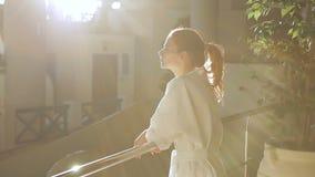 Het portret van jonge vrouw die zich op het balkon binnen het complexe luxekuuroord bevindt stock videobeelden