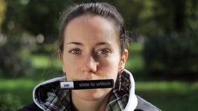 Het portret van jonge vrouw met naambord sticked aan haar mond bekijkend camera stock videobeelden