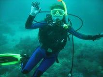 Het portret van jonge vrouwenscuba-duiker onder water Zij is in volledig vrij duikenmateriaal: masker, regelgever, BCD Zij toont  royalty-vrije stock afbeelding