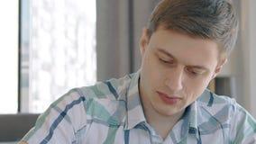 Het portret van jonge zekere zakenman werkt zitting in modern binnenland stock videobeelden