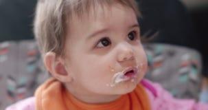 het portret van 4K Cinematic van een meisje die van de 10 maand oud baby lepelt gevoede yoghurt zijn stock videobeelden