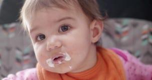 het portret van 4K Cinematic van een meisje die van de 10 maand oud baby lepelt gevoede yoghurt zijn stock footage
