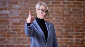Het portret van Kaukasische blonde kortharige vrouw in glazen die vinger-omhoog gesturing te tonen als bricken muurachtergrond stock videobeelden