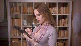 Het portret van het Kaukasische wavy-haired blondeleraar werken met tablet draait aan camera bij bibliotheek stock video