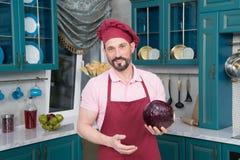 Het portret van Kerel bereidde verse groenten aan kok voor Gebaarde jonge kerel in schort op keuken royalty-vrije stock fotografie