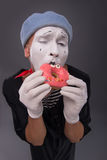 Het portret van knap mannetje bootst het eten van een smakelijk roze na Stock Afbeelding
