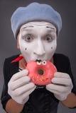 Het portret van knap mannetje bootst het eten van een smakelijk roze na Royalty-vrije Stock Fotografie
