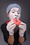 Het portret van knap mannetje bootst het eten van een smakelijk roze na Royalty-vrije Stock Afbeelding