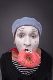 Het portret van knap mannetje bootst het eten van een smakelijk roze na Royalty-vrije Stock Afbeeldingen