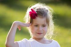 Het portret van leuk klein grappig blond meisje met aardige grijze ogen en rood nam in haar met juist die wapen toe in begroeting royalty-vrije stock afbeeldingen