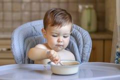Het portret van leuk weinig babyjongen houdt lepel in zijn hand en eet havermoutpap van de kom royalty-vrije stock fotografie