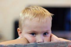 Het portret van leuk weinig Kaukasische jongen met licht gouden haar en blauwe ogen, met melancholische indruk, die omhoog zijn h royalty-vrije stock foto's